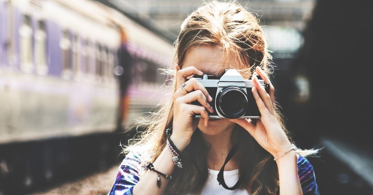 girl with camera and train in background
